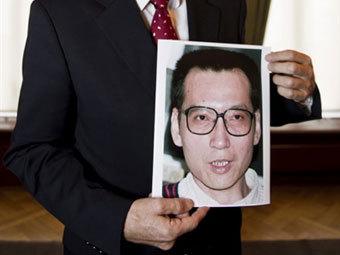 Портрет Лю Сяобо в руках у председателя Нобелевского комитета. Фото ©AFP