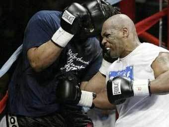 Майк Тайсон наносит удар Кори Сандерсу.  Фото Reuters.