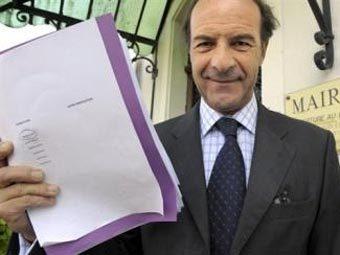Мэр Клод Беллей с документами о переименовании жителей Ванту. Фото AFP