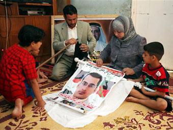 Семья Мунтазера аль-Зайди с портретом журналиста. Фото ©AP