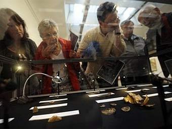 Посетители выставки осматривают клад, найденный в Стаффордшире. Фото ©AFP