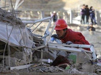 Спасатель у разрушенного здания. Фото ©AFP