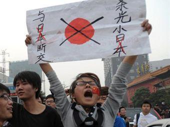 """Китайская демонстрантка на акции протеста держит плакат с надписью """"Убейте всех японцев, порвите с Японией все отношения"""". Фото ©AFP"""