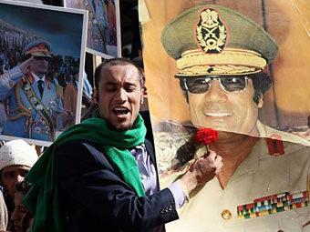 Сторонник Каддафи с портретом полковника. Фото ©AFP