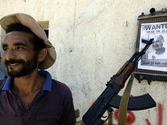 Повстанец указывает на объявление о розыске Каддафи в Триполи. Архивное фото ©AFP