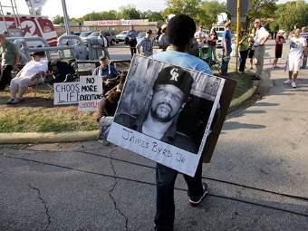Мужчина несет фото убитого Джеймса Берда. Фото ©AP