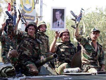 Сирийские военнослужащие с портретом Башара Асада. Фото ©AFP