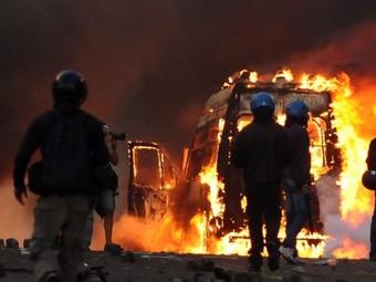 Полицейские у горящего автомобиля в Риме 15 октября 2011 года. Фото ©AFP
