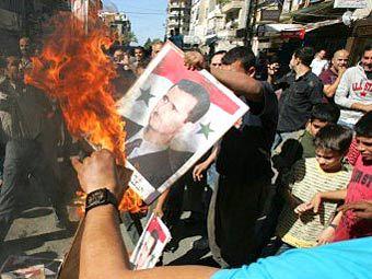 Демонстранты сжигают портрет Башара Асада. Фото ©AFP