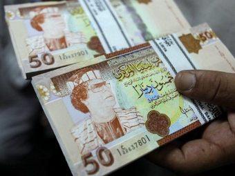 Ливийские динары с изображением Каддафи. Фото ©AFP