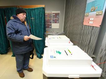 Мужчина с бюллетенем у электронных урн для голосования. Фото РИА Новости, Евгений Козырев