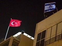 Турецкий флаг над зданием посольства Турции в Тель-Авиве и флаг Израиля в руках демонстрантов. Архивное фото (c)AFP