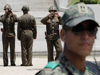 Северокорейские пограничники (на заднем плане) и южнокорейский пограничник. Фото ©AFP