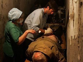 Врачи оказывают помощь раненому в подвале в Цхинвали. Фото AFP.