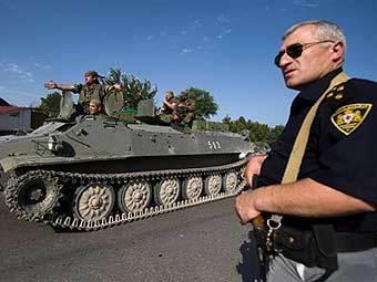 Полицейский на фоне грузинской военной колонны. Фото AFP.